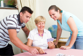 Caregivers and elderly playing cards