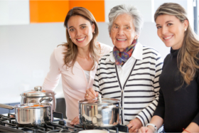 Caregivers accompanying an elderly in the kitchen