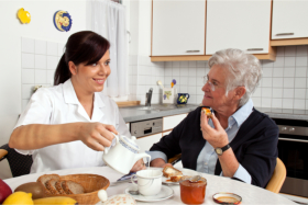 Caregiver pouring milk on a cup while listening to an elderly