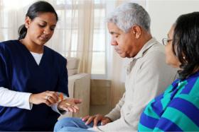 Caregiver giving medicine to elderlies